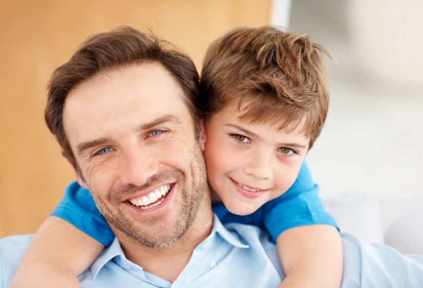 Picture of father smiling, with young son hugging him around the neck