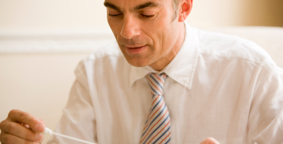 A man in a white shirt and a tie looking at a paternity test
