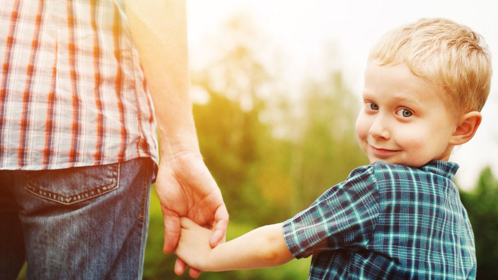 Happy child holding Dad's hand