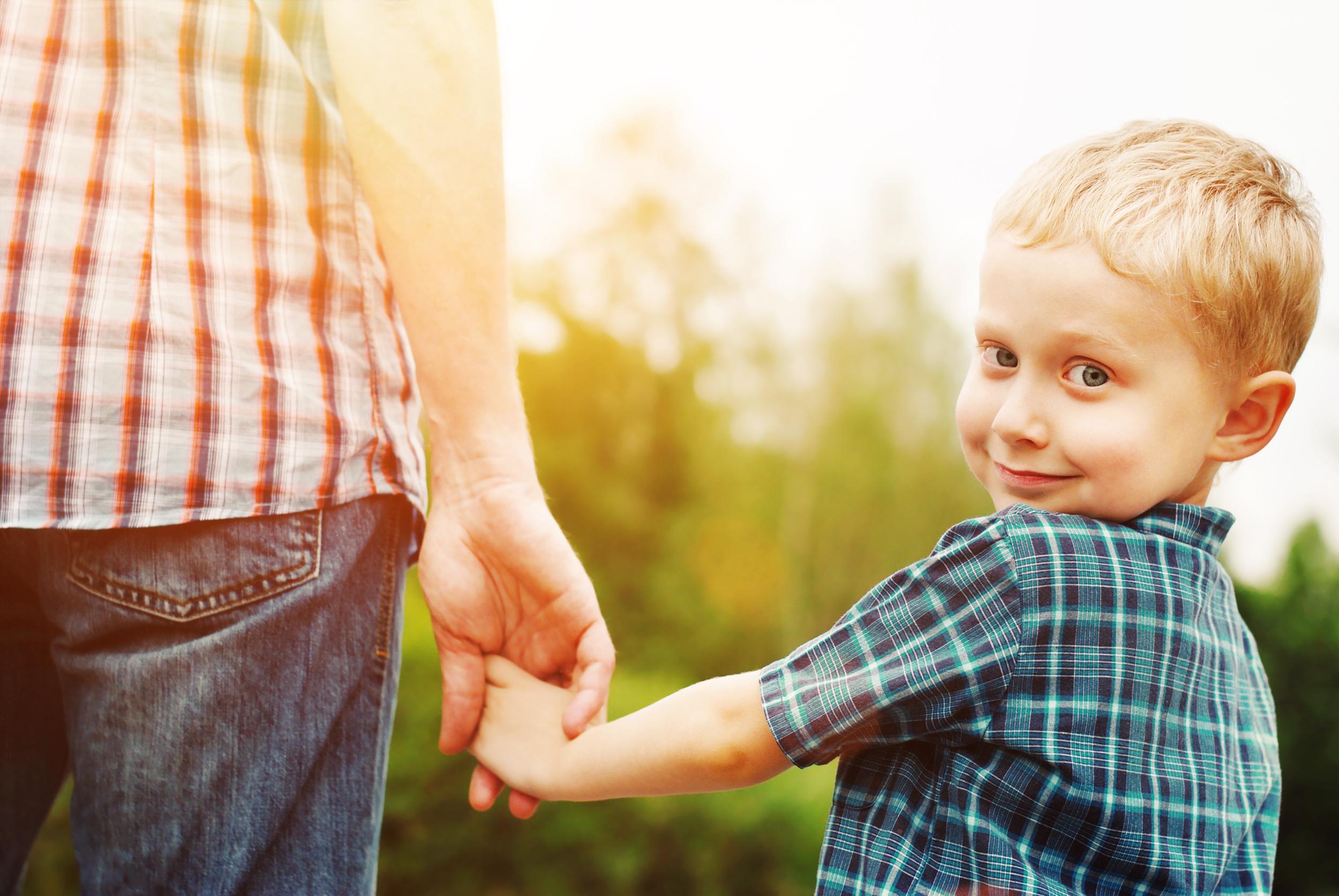 Happy child holding Dad's hand